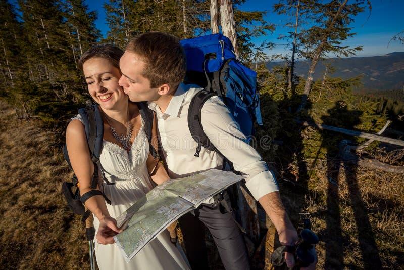 Pares do turista do casamento que beijam com o mapa nas mãos Lua de mel nas montanhas foto de stock