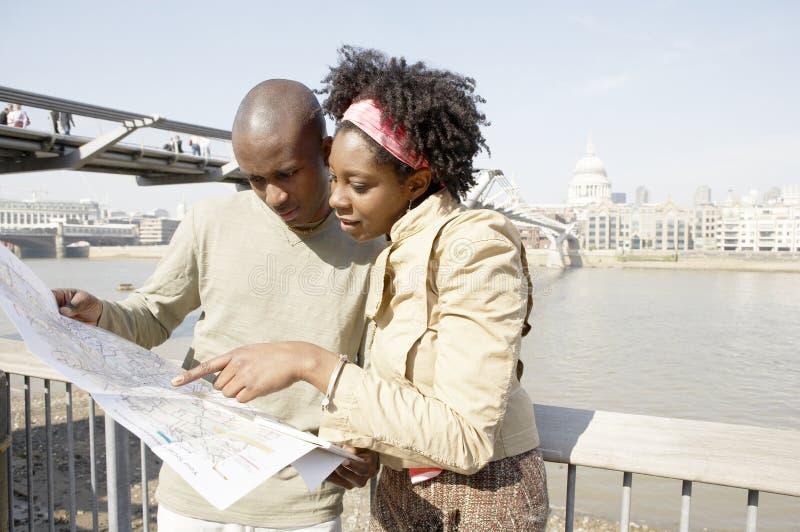 Pares do turista em Londres com mapa. imagens de stock