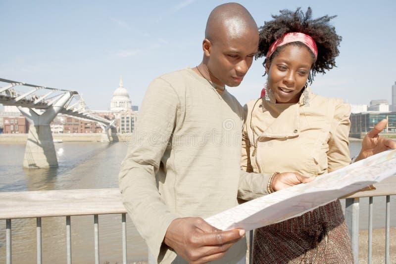 Pares do turista em Londres com mapa. imagem de stock