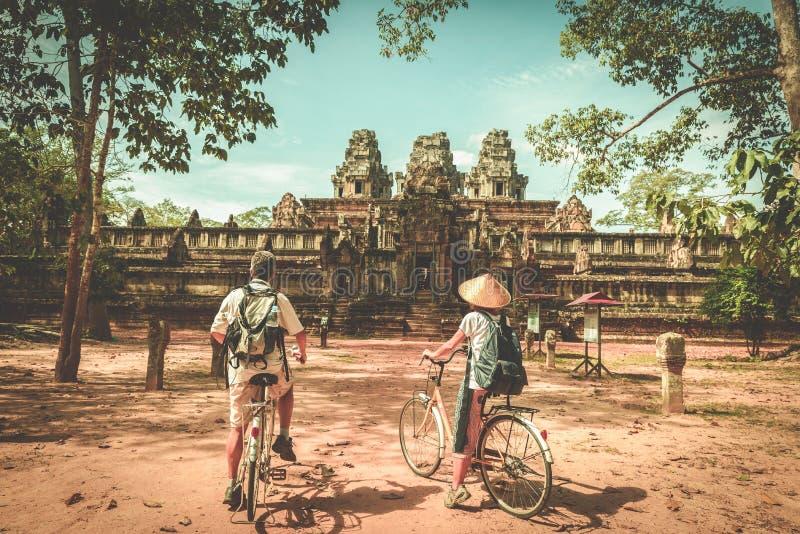 Pares do turista que dão um ciclo em torno do templo de Angkor, Camboja Ruínas da construção de Ta Keo na selva Viagem amigável d foto de stock