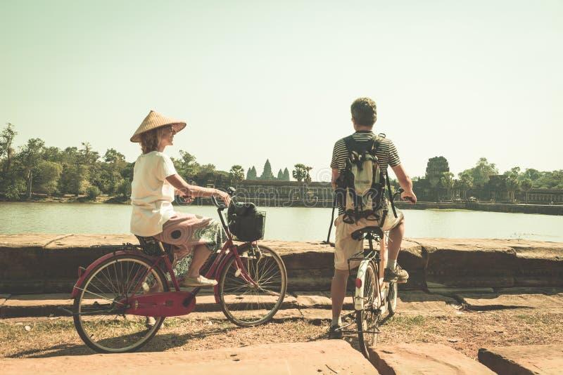 Pares do turista que d?o um ciclo no templo de Angkor, Camboja A fachada principal de Angkor Wat refletiu na lagoa de ?gua Viagem foto de stock