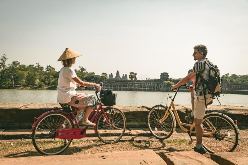 Pares do turista que d?o um ciclo no templo de Angkor, Camboja A fachada principal de Angkor Wat refletiu na lagoa de ?gua Viagem imagens de stock