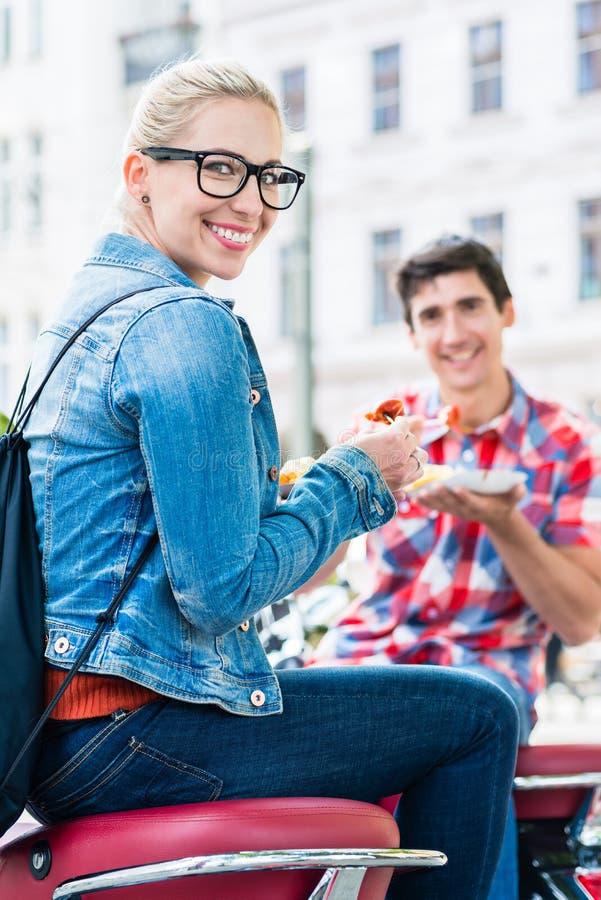Pares do turista que tomam o resto durante a excursão do 'trotinette' que come o currywurst imagem de stock royalty free