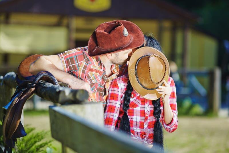 Pares do vaqueiro que beijam um indivíduo e uma menina em chapéus de vaqueiro fotos de stock