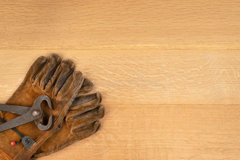Pares do vintage de cortar alicates das pinças e fundo da madeira das luvas do trabalho fotos de stock royalty free