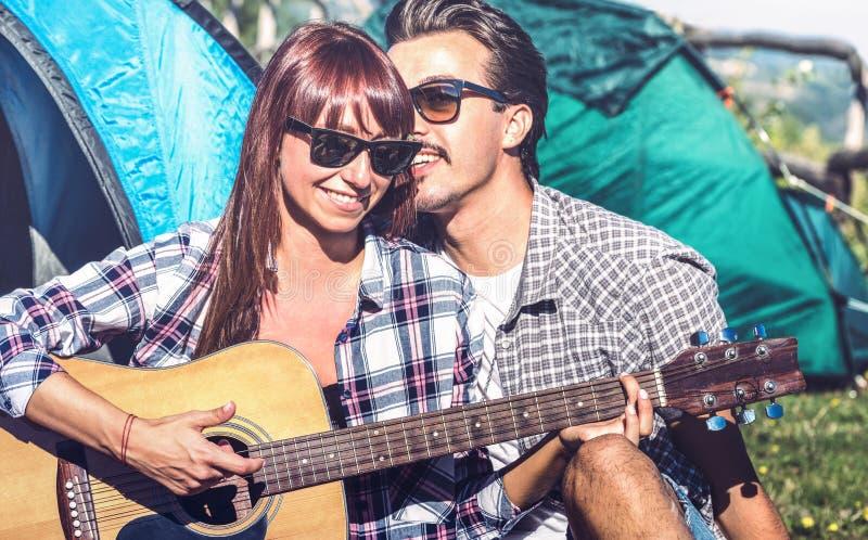 Pares dos amantes que têm cheering exterior do divertimento no lugar de acampamento com guitarra do vintage - jovem que aprecia h imagens de stock