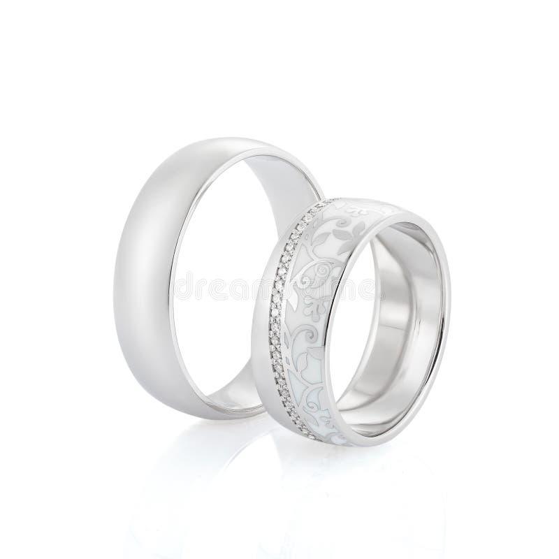 Pares dos anéis de prata do casamento da elegância isolados no fundo branco O anel das mulheres com esmalte, os diamantes e desig fotos de stock royalty free