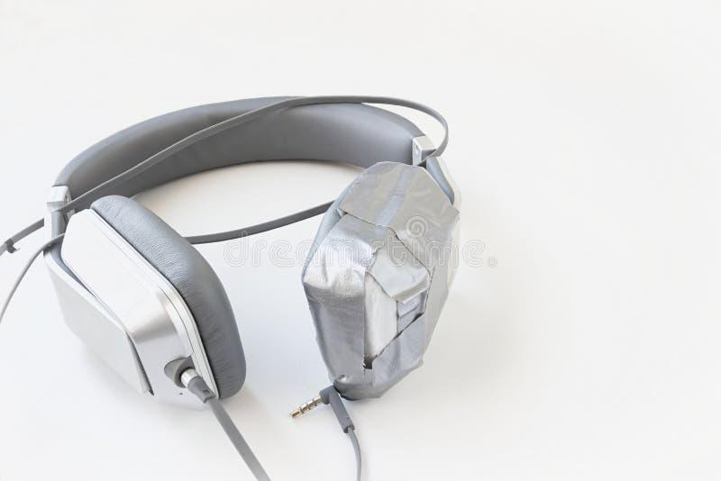 Pares dos fones de ouvido quebrados de prata fixados com fita adesiva foto de stock