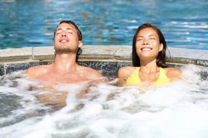 Pares dos termas que relaxam apreciando a banheira de hidromassagem do Jacuzzi imagens de stock royalty free
