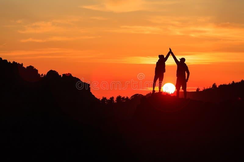 Pares dos trabalhos de equipa que comemoram no por do sol inspirador das montanhas foto de stock royalty free