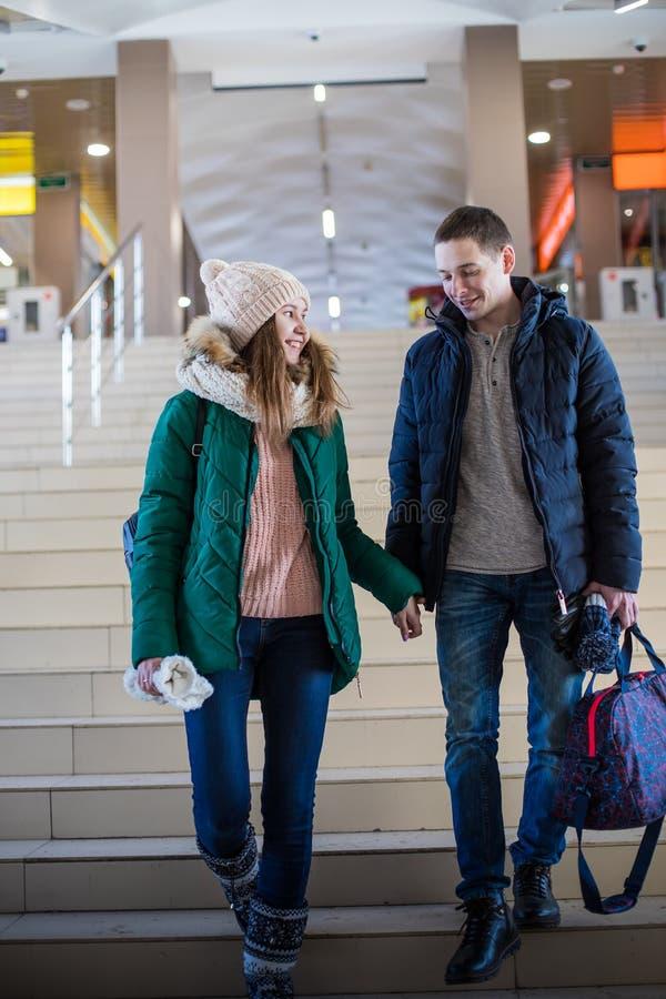 Pares dos viajantes na roupa morna nas etapas na sala da estação imagens de stock royalty free