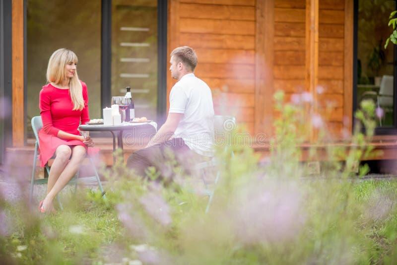 Pares durante una cena en el patio trasero de la casa foto de archivo libre de regalías