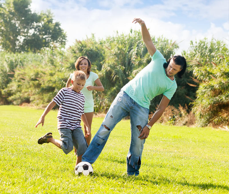 Pares e adolescente que jogam no parque foto de stock royalty free