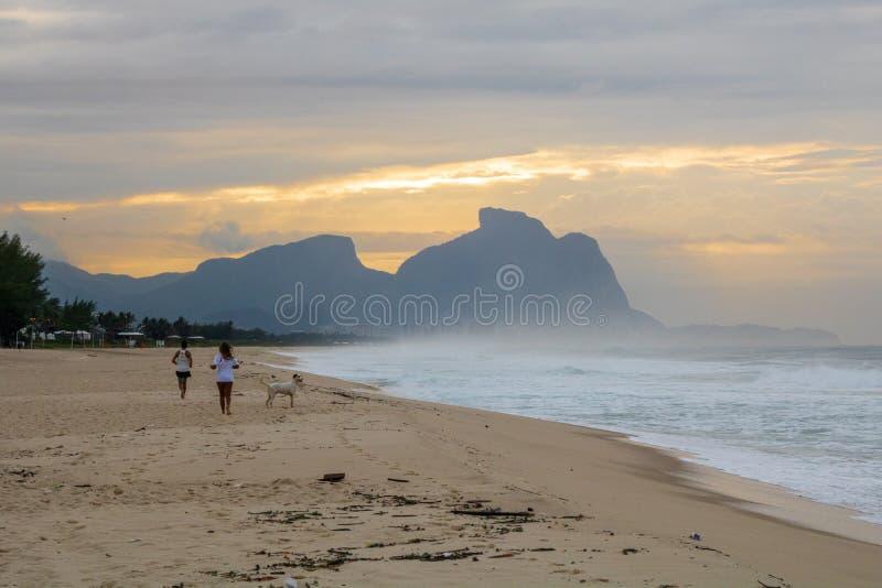 Pares e cão que correm na praia de Barra da Tijuca em um alvorecer bonito com a pedra de Gavea no fundo - Rio de Jane foto de stock