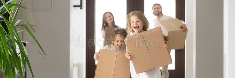 Pares e crianças com as caixas que correm na casa nova imagem de stock
