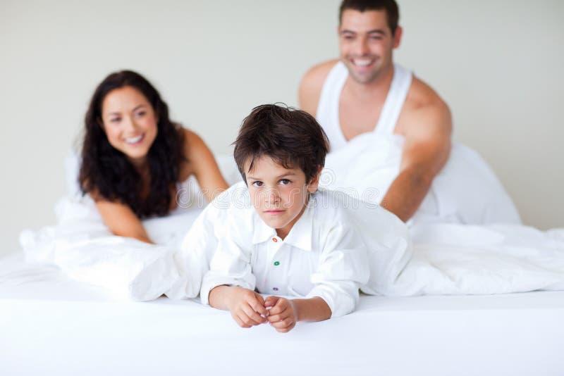 Pares e filho que apreciam junto na cama fotografia de stock royalty free