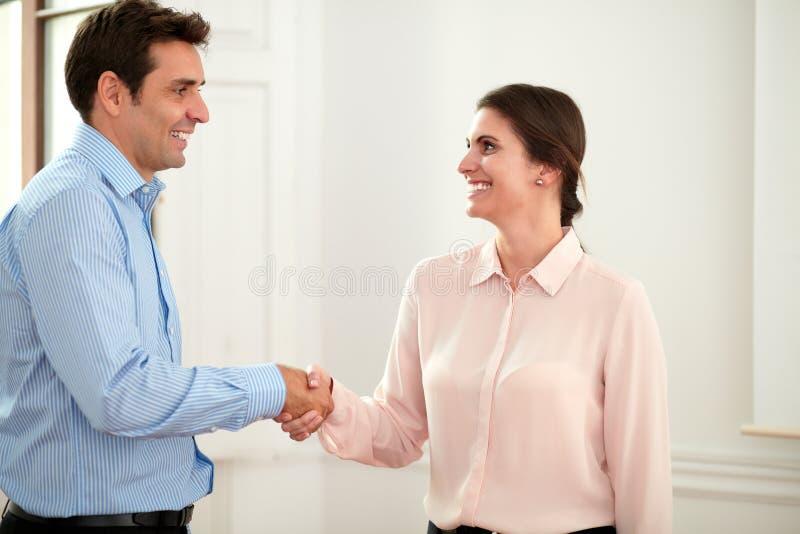 Pares ejecutivos que dan las manos que saludan y que sonríen imagenes de archivo