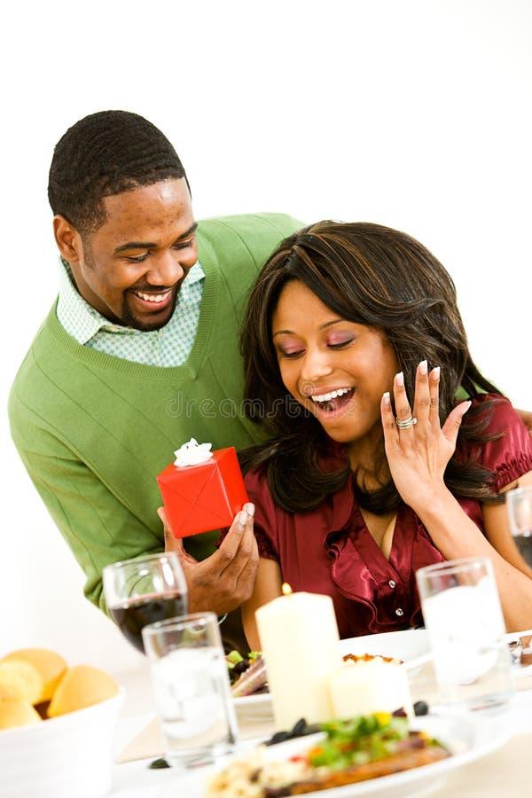 Pares: El hombre sorprende a la mujer con el presente en la cena foto de archivo