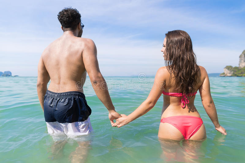 Pares el vacaciones de verano de la playa, gente joven en agua, mujer del hombre que sostiene el océano del mar de las manos fotografía de archivo libre de regalías