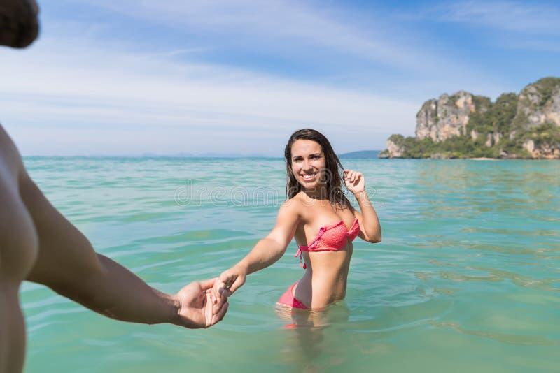 Pares el vacaciones de verano de la playa, gente joven en agua, mujer que sostiene el océano del mar de la mano del hombre fotografía de archivo