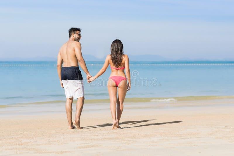 Pares el vacaciones de verano de la playa, gente joven en amor que camina, mujer del hombre que sostiene el océano del mar de las fotografía de archivo libre de regalías