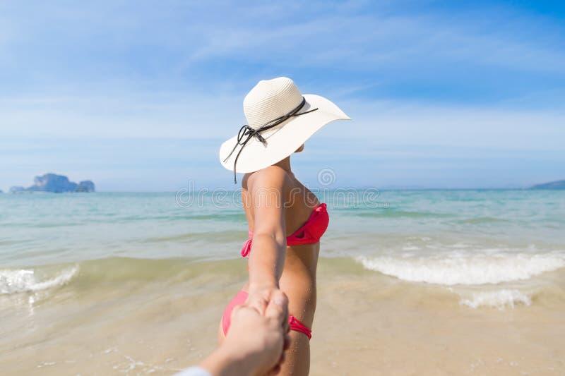 Pares el vacaciones de verano de la playa, gente joven en amor que camina, mujer que sostiene el océano del mar de la mano del ho foto de archivo