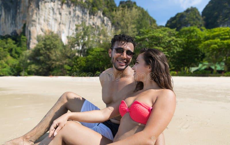 Pares el vacaciones de verano de la playa, gente joven que se sienta en la arena, océano del mar de la mujer del hombre fotos de archivo libres de regalías