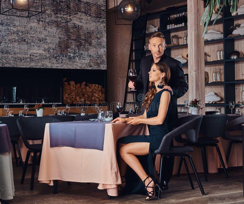 Pares elegante vestidos - varón elegante hermoso y mujer morena encantadora durante la datación en un restaurante de lujo imágenes de archivo libres de regalías