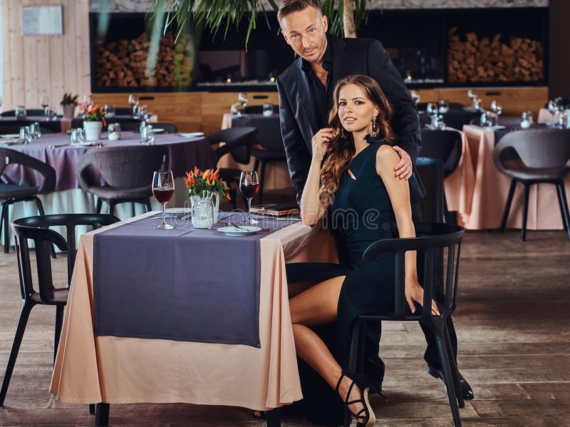 Pares elegante vestidos - varón elegante hermoso y mujer morena encantadora durante la datación en un restaurante de lujo imagen de archivo libre de regalías