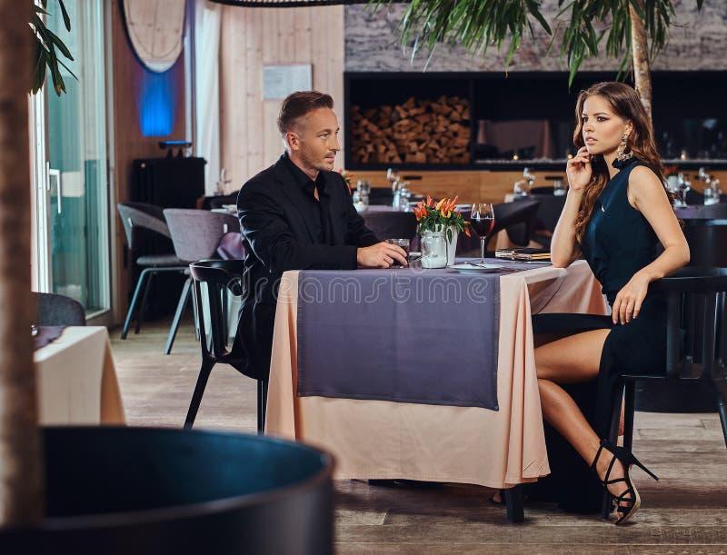 Pares elegante vestidos - varón elegante hermoso y mujer morena encantadora que se sientan junto en un restaurante de lujo fotos de archivo libres de regalías