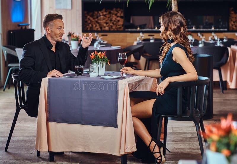 Pares elegante vestidos - varón elegante hermoso y mujer morena encantadora que se sientan junto y negociaciones durante imágenes de archivo libres de regalías