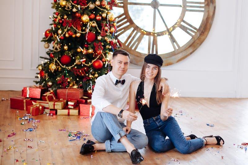 Pares elegantes alegres con la bengala que liga cerca del árbol de navidad adornado en casa antes de partido foto de archivo