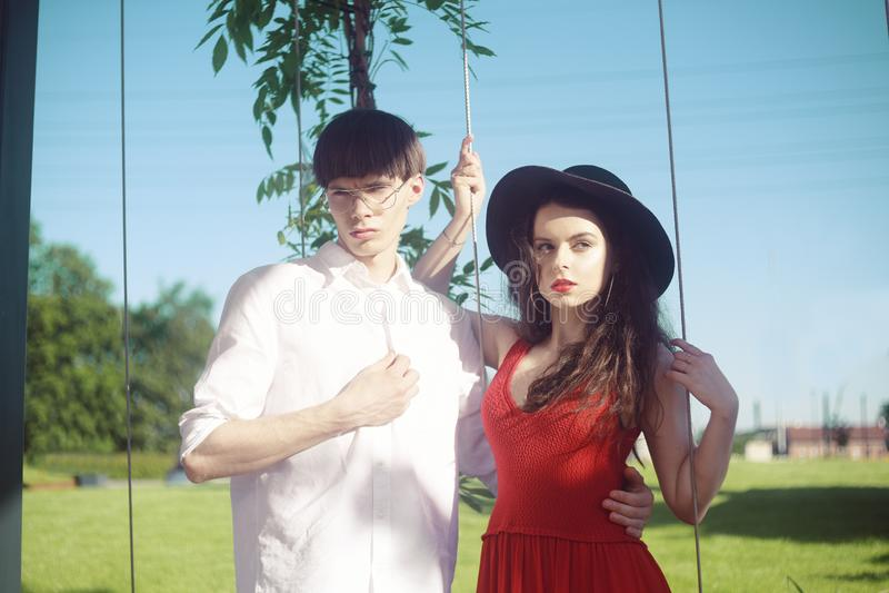 Pares elegantes bonitos contra o céu e a praia Modernos elegantes Menina em um vestido vermelho e em um chapéu grande preto foto de stock royalty free