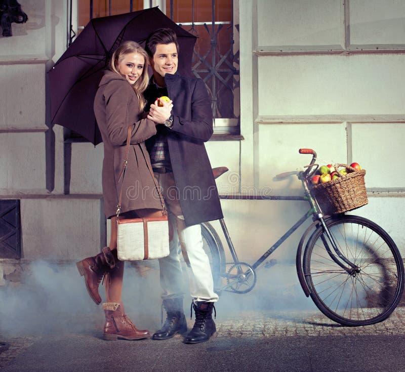 Pares elegantes con el paraguas en la tarde lluviosa imagen de archivo