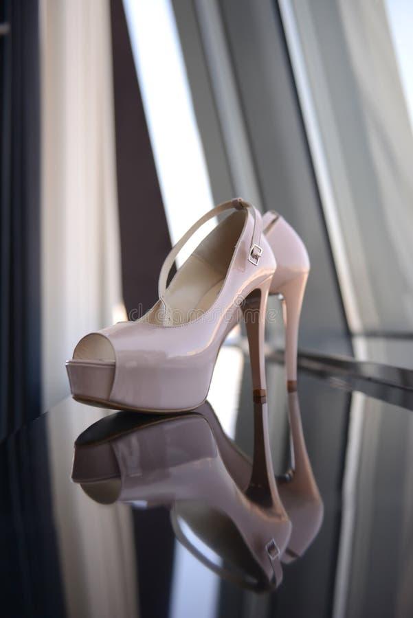Pares elegantes das sapatas nupciais brancas em um espelho fotos de stock royalty free