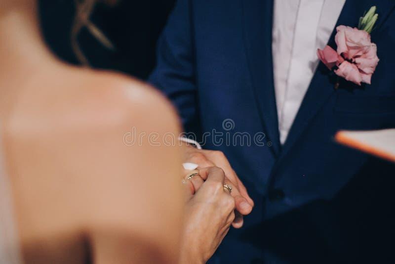 Pares elegantes de la boda que intercambian los anillos de bodas en el matrimonio santo en iglesia Opinión cosechada la novia y e imagen de archivo libre de regalías