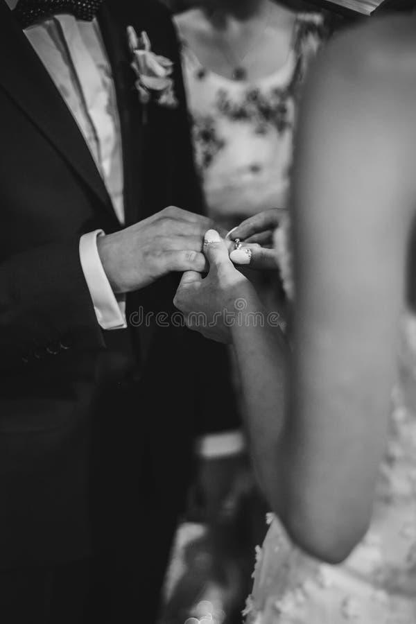 Pares elegantes de la boda que intercambian los anillos de bodas en el matrimonio santo en iglesia Opinión cosechada la novia y e imagenes de archivo