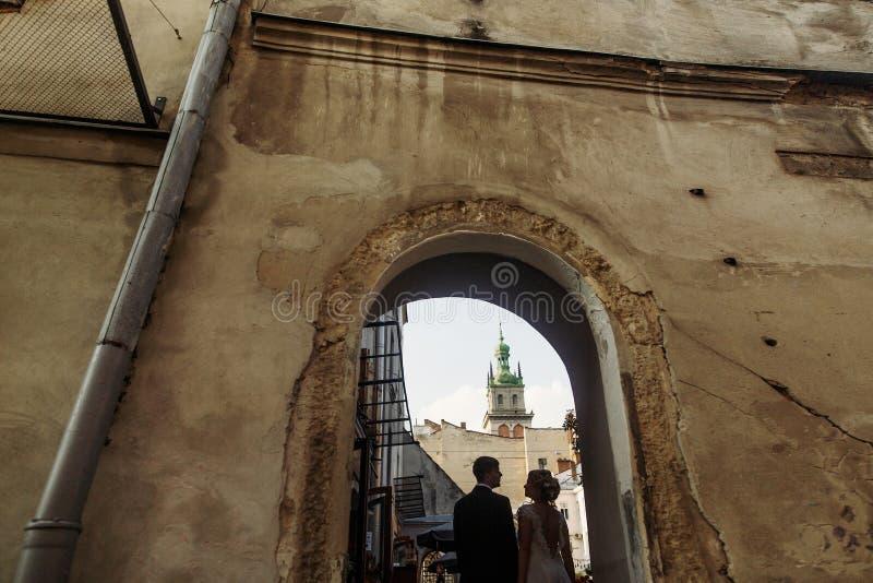 Pares elegantes de la boda que presentan en la calle europea vieja Lviv de la ciudad imagenes de archivo