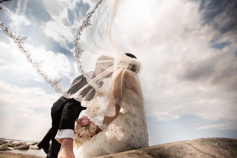 Pares elegantes de la boda que se colocan en orilla de mar Los recienes casados est fotografía de archivo