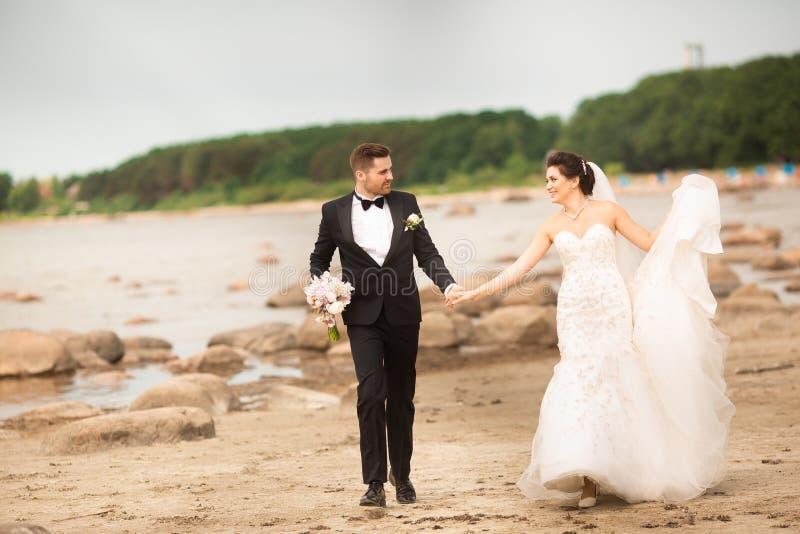 Pares elegantes de la boda que se colocan en orilla de mar Los recienes casados est fotos de archivo