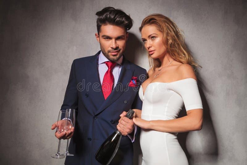 Pares elegantes de la moda listos para beber el champán imagenes de archivo