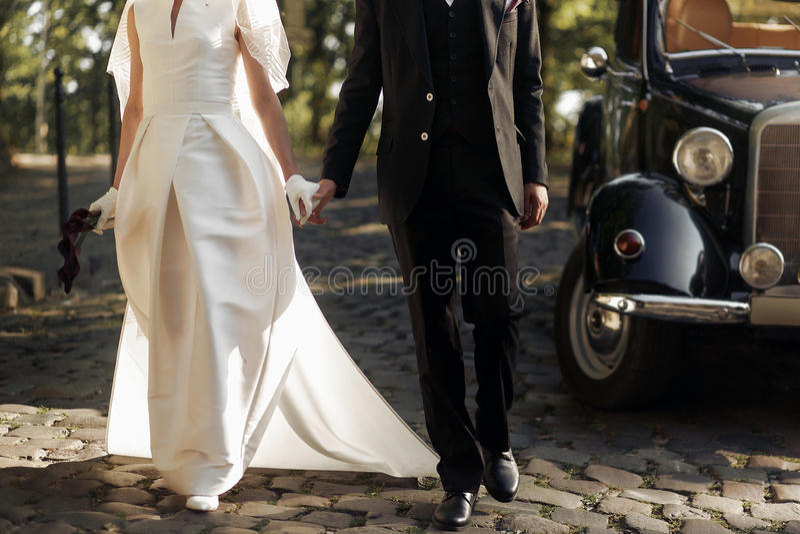Pares elegantes de lujo de la boda que caminan y que sostienen ascendente cercano de las manos imagenes de archivo