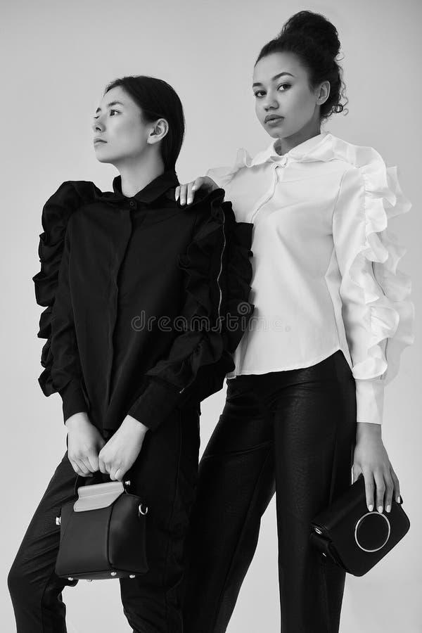 Pares elegantes de mujeres negras y asiáticas en negro de moda y foto de archivo
