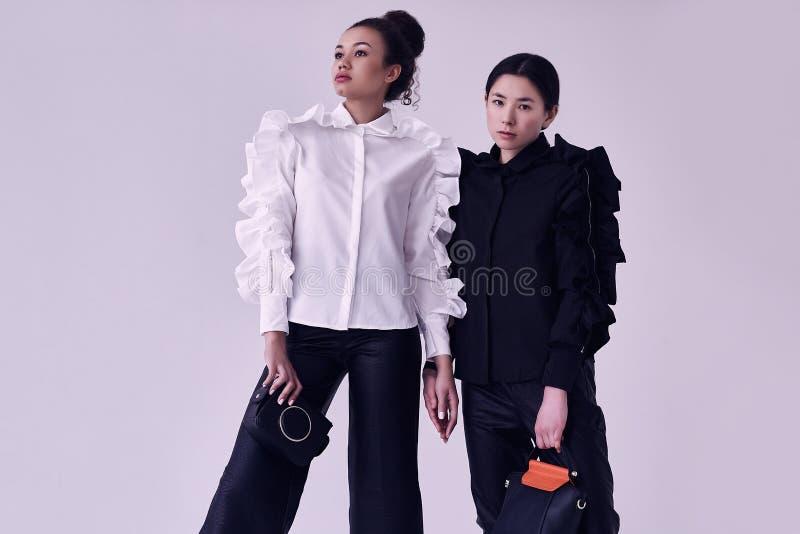 Pares elegantes de mujeres negras y asiáticas en trajes blancos y negros de moda fotos de archivo