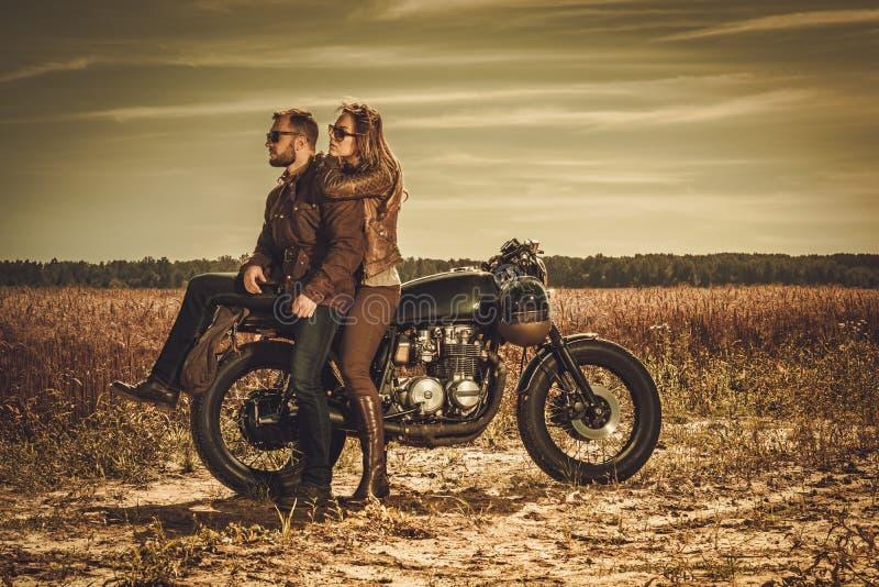 Pares elegantes del corredor del café en las motocicletas de encargo del vintage en un campo fotos de archivo libres de regalías