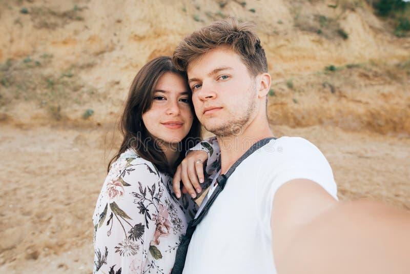 Pares elegantes del inconformista que toman el selfie en la playa en el acantilado arenoso en el mar Vacaciones de verano Retrato imagen de archivo