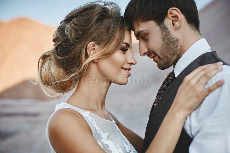 Pares elegantes e bonitos, menina modelo loura feliz com penteado à moda, em um vestido branco do laço e à moda fotos de stock