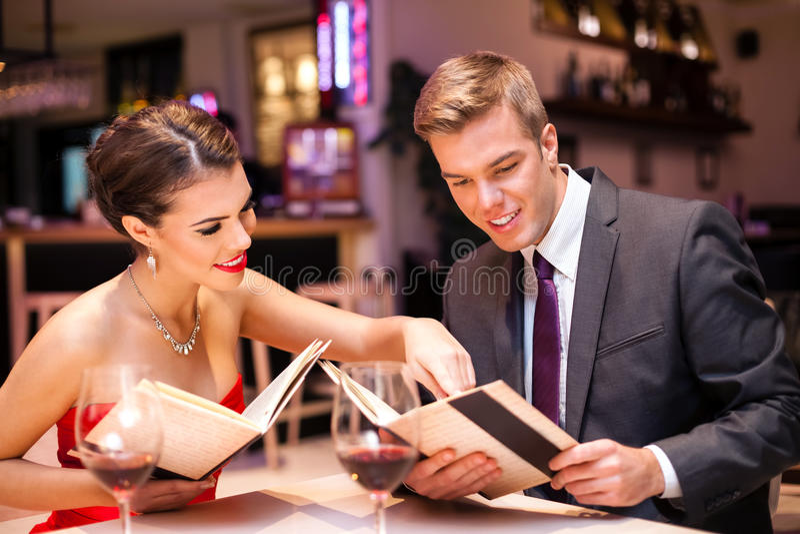 Pares elegantes en restaurante imagen de archivo
