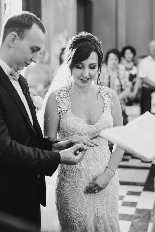 Pares elegantes felices de la boda que intercambian los anillos de bodas durante matrimonio santo en iglesia Novia y novio que po imagen de archivo