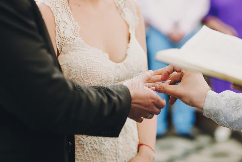 Pares elegantes felices de la boda que intercambian los anillos de bodas durante matrimonio santo en iglesia Novia y novio que po imágenes de archivo libres de regalías